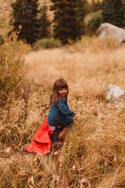 Young girl climbing through long grass, Mineral King, Sequoia National Park, California, USA