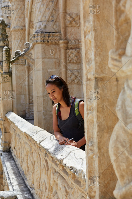 Young woman looking at view from upper courtyard level of Mosteiro dos Jeronimos (Jeronimos Monastery) in Lisbon, Portugal