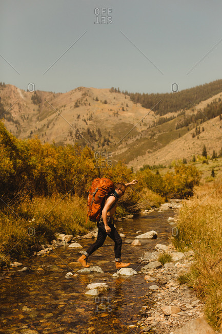 Man, wearing backpack, crossing creek, Mineral King, Sequoia National Park, California, USA