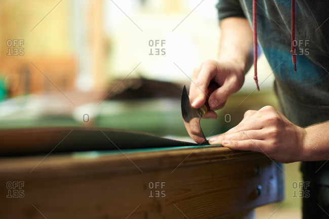 Male worker using french saddler's leather cutting tool in workshop, mid section