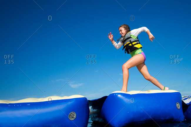 Girl running across inflatable platforms, Seaside Heights, New Jersey, USA