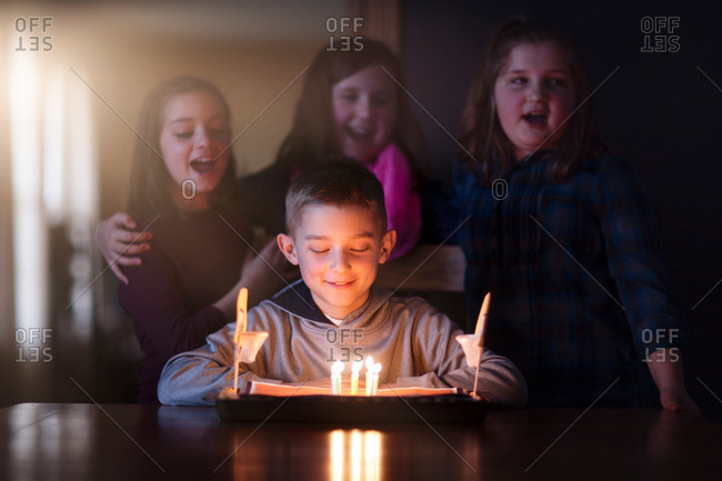 Boy surrounded by friends looking at birthday cake smiling