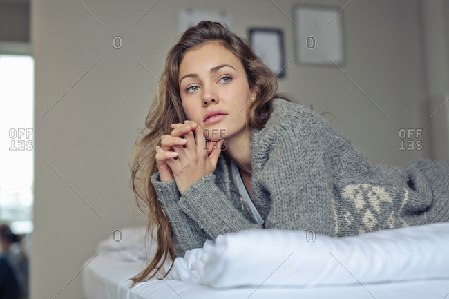 Woman lying down resting on elbows looking away