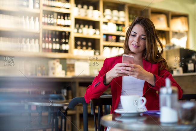 Young woman sitting in cafe reading smartphone update