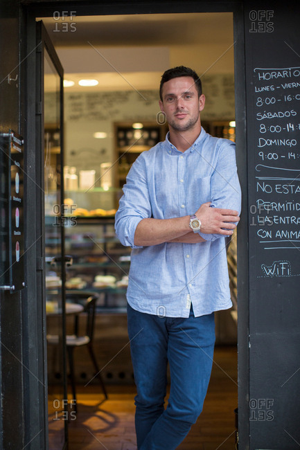 Portrait of mid adult male cafe owner leaning against cafe doorway