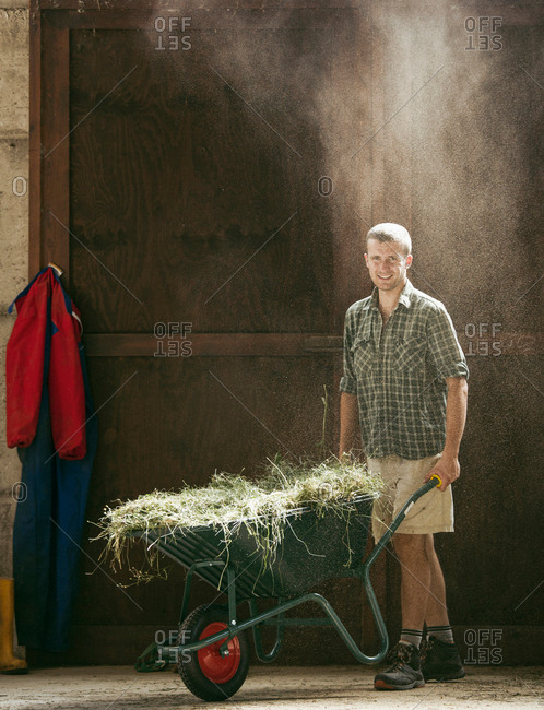 Portrait of young male farmworker with wheelbarrow in dusty farm barn