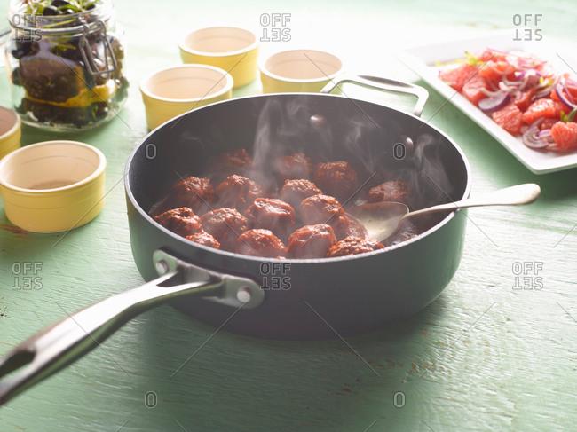 Saucepan of steaming Greek meatballs on table