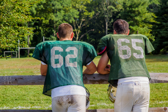 Rear view of two teenage male American football players leaning on playing field fence