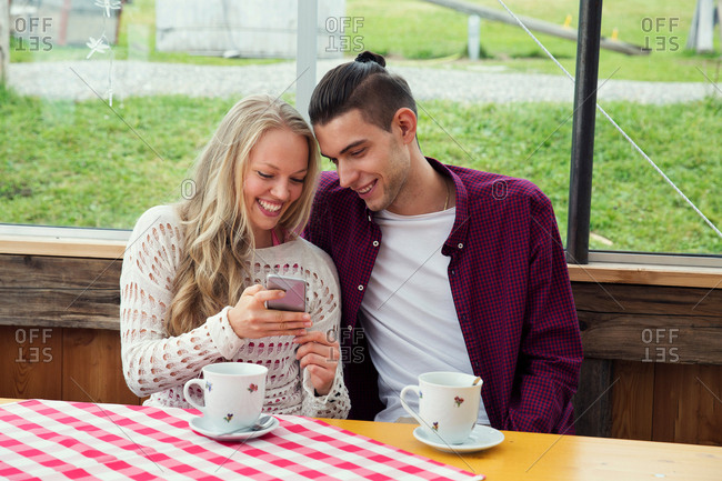 Young couple looking at smartphone update in cafe