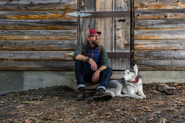 Man with dog resting by wooden cabin, Walton lake, Oregon, USA