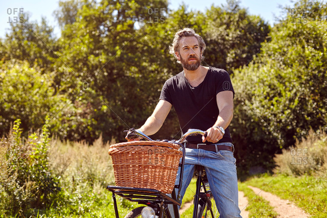 Mid adult man on bicycle gazing from rural dirt track