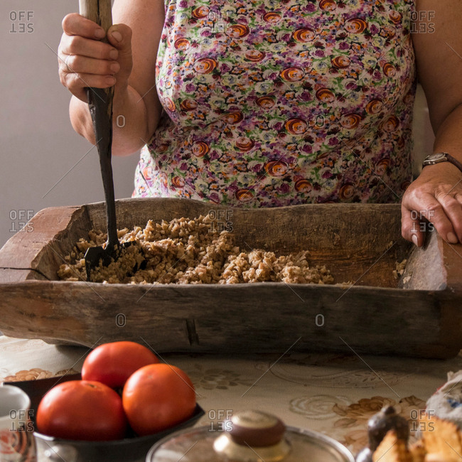 Cropped view of woman chopping food in wooden chopping board, Ural, Russia