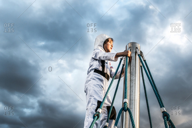 Boy in astronaut costume gazing from top of climbing frame against dramatic sky