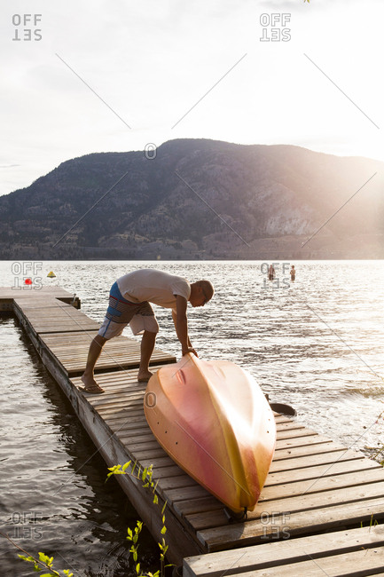 Man turning over boat on pier, Penticton, Canada