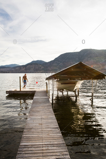 Man with boat moored on pier, Penticton, Canada
