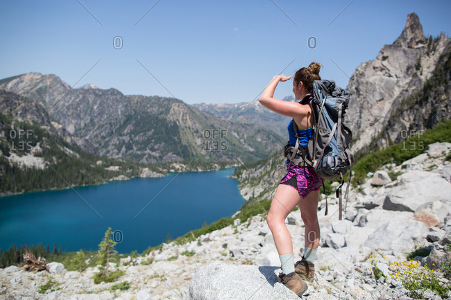 Young woman standing on rocks, looking at view, The Enchantments, Alpine Lakes Wilderness, Washington, USA