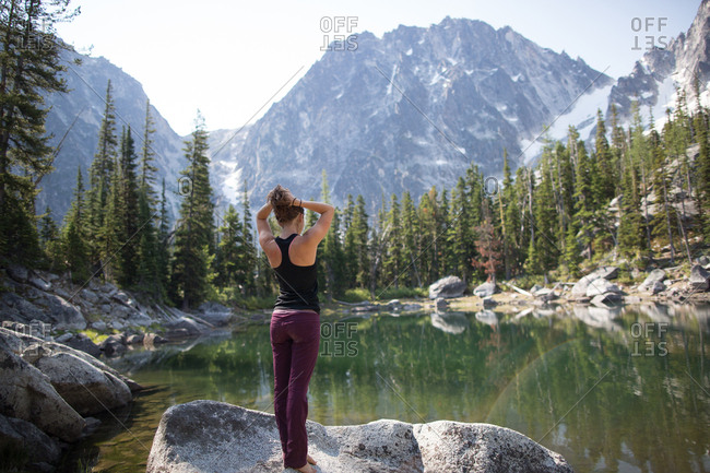 Young woman standing on rock beside lake, looking at view, The Enchantments, Alpine Lakes Wilderness, Washington, USA