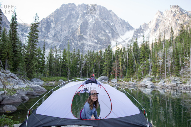 Young woman sitting in tent beside lake, The Enchantments, Alpine Lakes Wilderness, Washington, USA