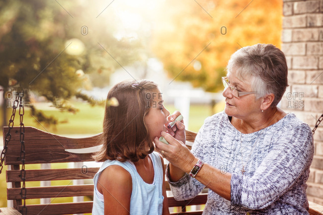 Grandmother and granddaughter sitting on porch swing, grandmother showing granddaughter how to apply lipstick