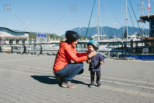 British Columbia, Canada - February 2, 2015: Mother putting protective helmet on son, British Columbia, Canada