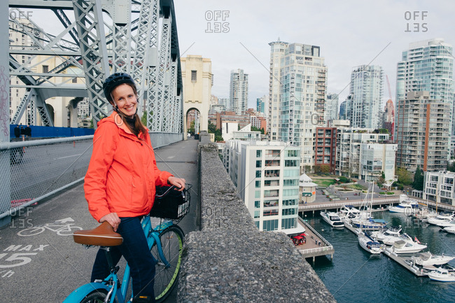 British Columbia, Canada - February 6, 2015: Portrait of young woman ready to ride bicycle on cycle path, Vancouver, British Columbia, Canada