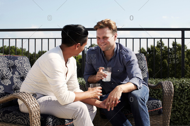 Homosexual couple enjoying a drink outdoors, face to face holding hands