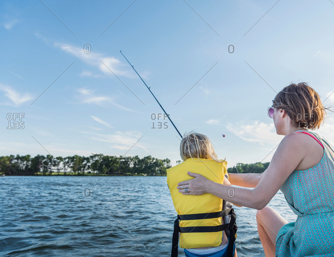 Mother and son wearing life jacket fishing