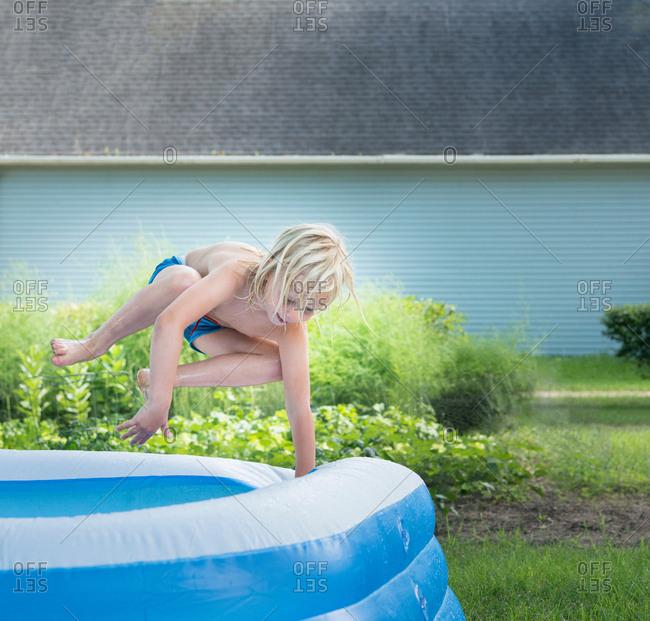 Boy jumping into paddling pool