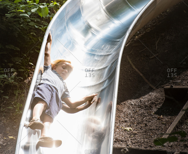 Boy sliding down playground slide