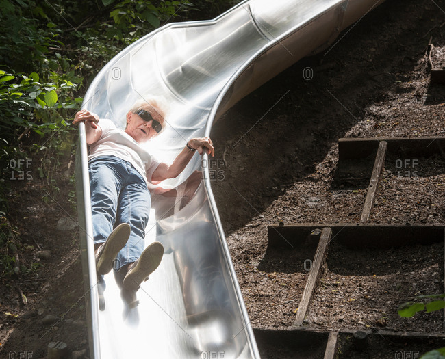 Woman sliding down playground slide