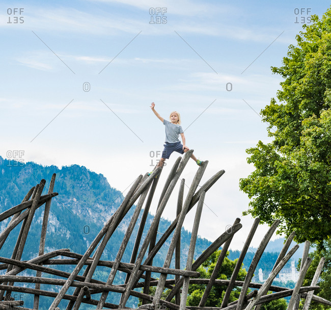 Boy standing on top of wooden structure in playground, Fuessen, Bavaria, Germany