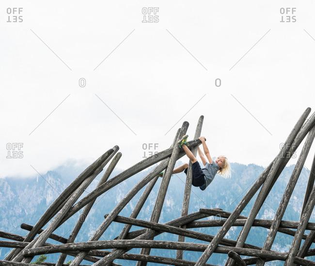 Boy climbing wooden structure in playground, Fuessen, Bavaria, Germany