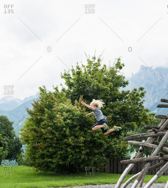 Boy in mid air jumping from wooden structure in playground, Fuessen, Bavaria, Germany