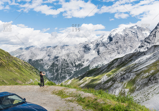 Rear view of woman photographing mountain, Passo di Stelvio, Stelvio, Italy