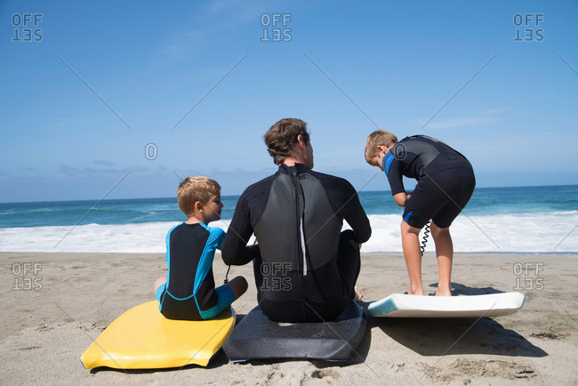Rear view of father and two sons practicing with bodyboards on beach, Laguna Beach, California, USA