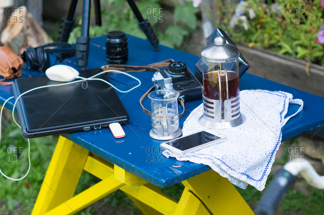 Camera equipment, laptop and cafeteria on table in garden