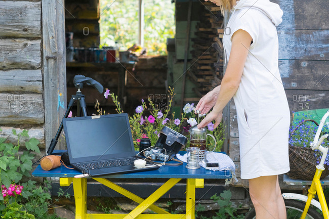 Woman using cafeteria outdoors, camera equipment and laptop on table next to cafeteria, mid section