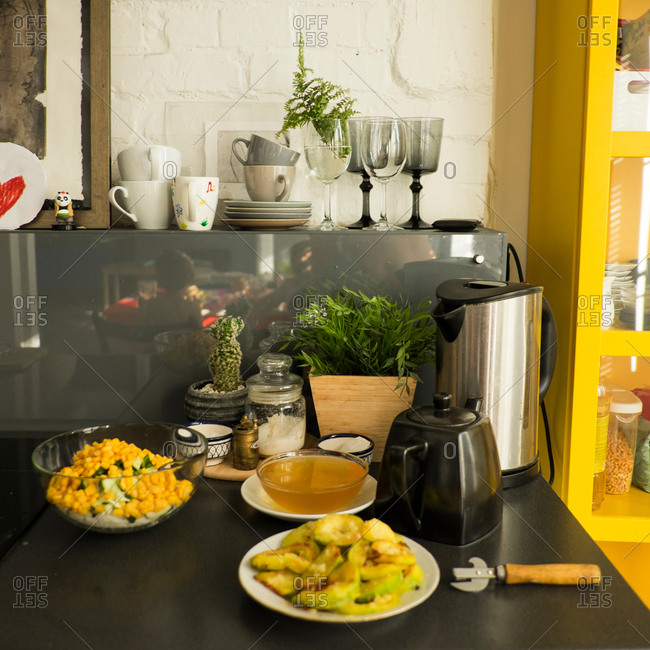 Kitchen interior, showing kitchen work surface with fried zucchini, honey and corn