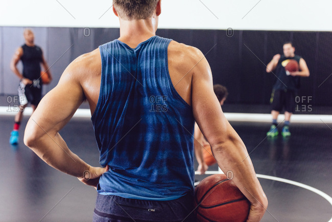 Rear view of male basketball player holding ball on court