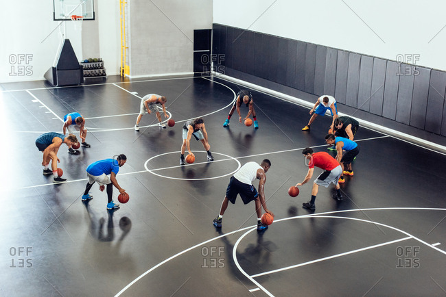 Male trainer and basketball team practicing on court