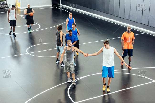 Male basketball team players shaking hands at basketball court