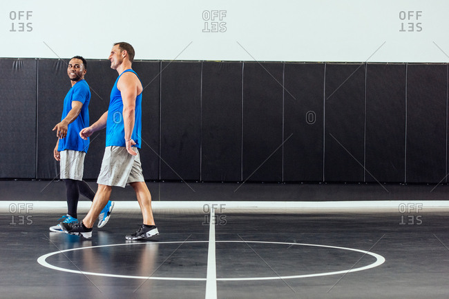 Male basketball players walking and talking on basketball court