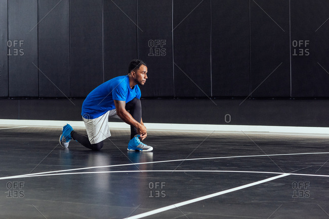 Male basketball player tying trainer laces on basketball court