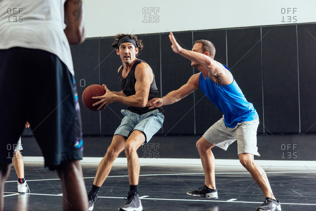 Male basketball players defending ball in basketball game