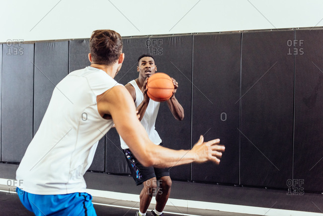 Two male basketball players practicing ball defence and aim on basketball court