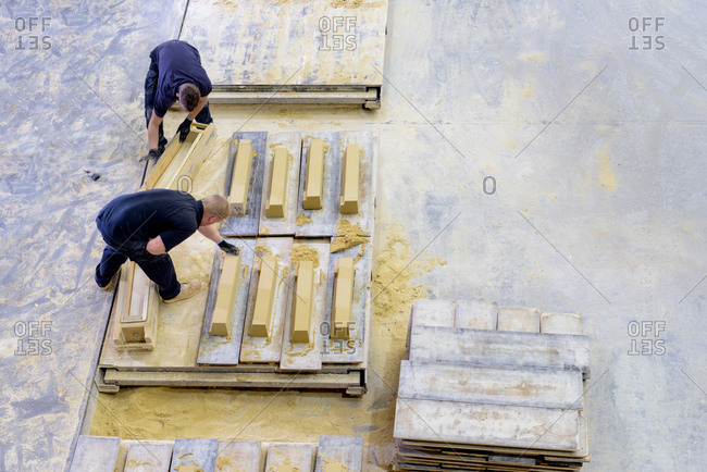 Overhead view of workers molding stone in architectural stone factory