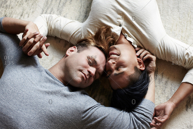 Overhead view of male gay couple lying on floor in opposite directions
