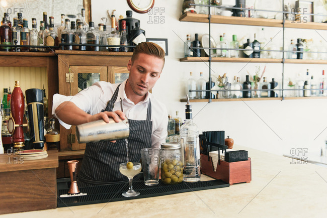 Male bartender pouring cocktail at cocktail bar