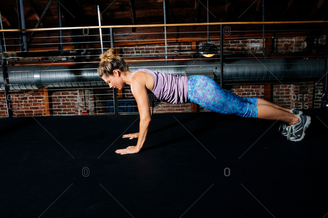 Side view of woman doing push ups