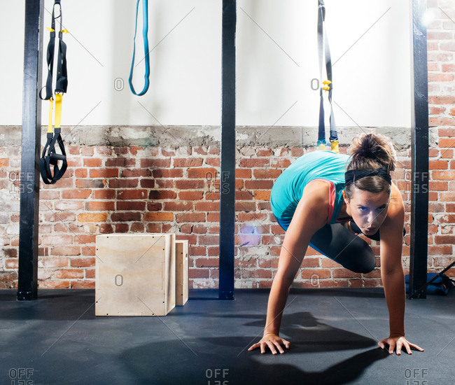 Woman with hands on floor exercising in gym